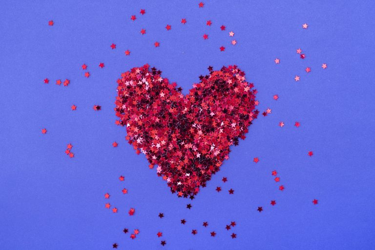 Heart shaped red sparkles on purple background